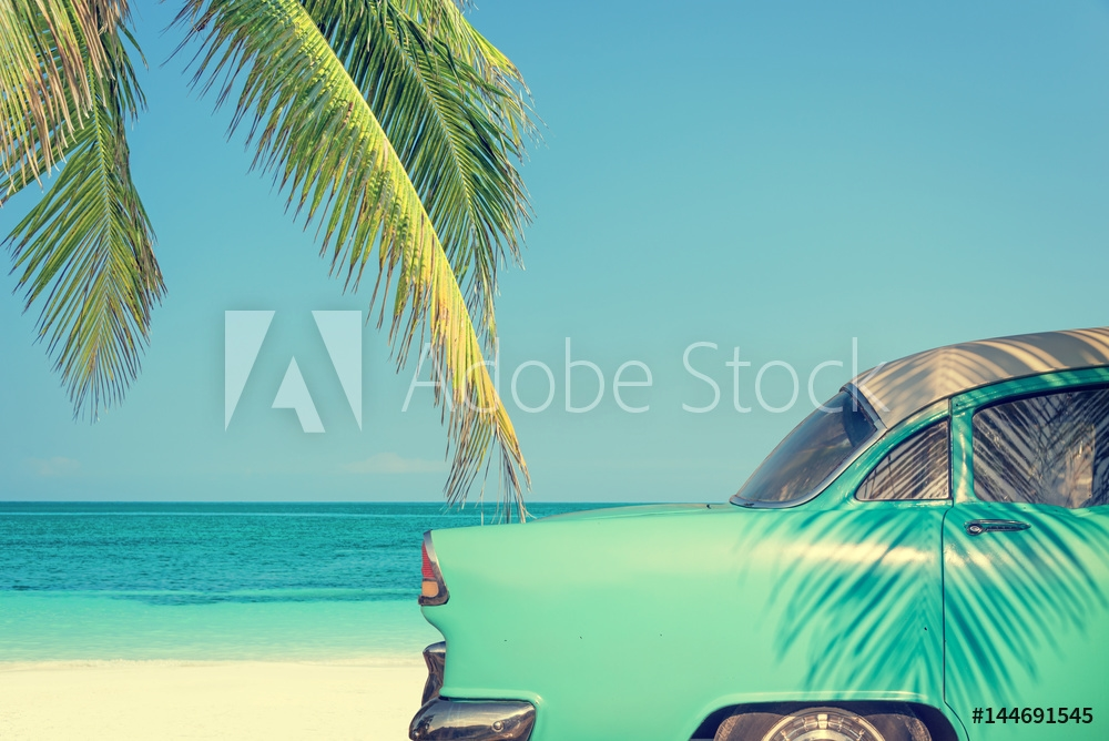 Picture of Classic car on a tropical beach with palm tree, vintage process